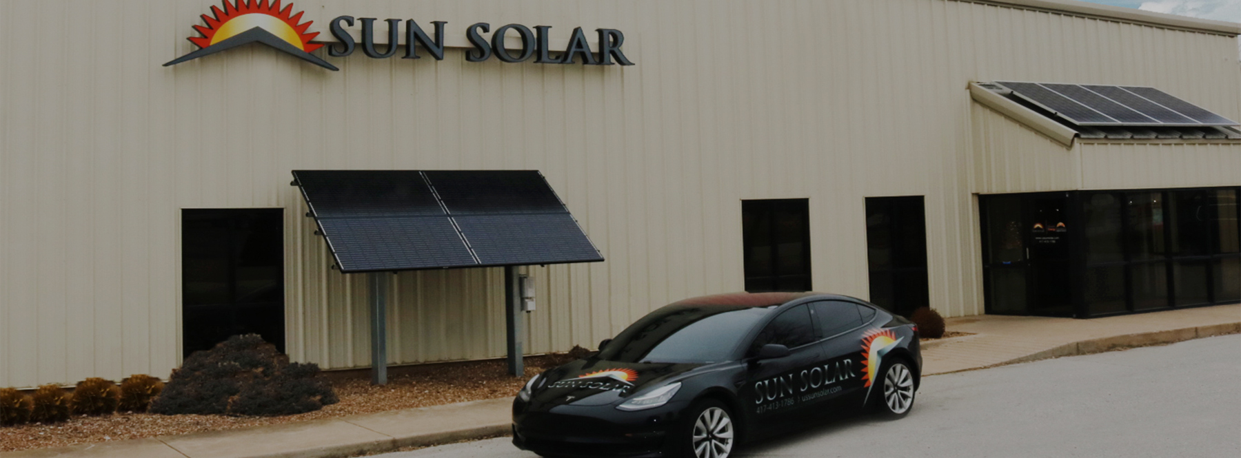Black Tesla Model 3 parked outside of a tan building, owned by Sun Solar a solar panel installer in Springfield, Missouri, with ground and roof mounted solar panels.